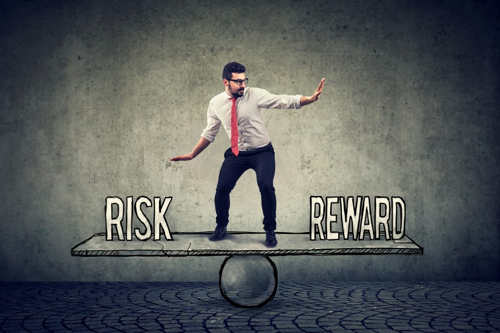 Skillful young business man balancing between reward and risk in challenging corporate environment