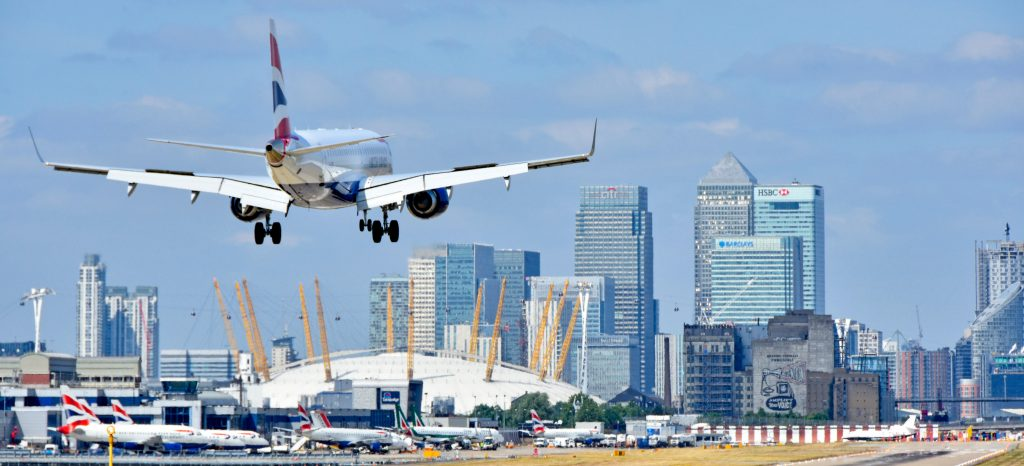 EWD91F British Airways flight landing at London City Airport Newham with O2 arena & Canary Wharf skyline Tower Hamlets East London Docklands England UK